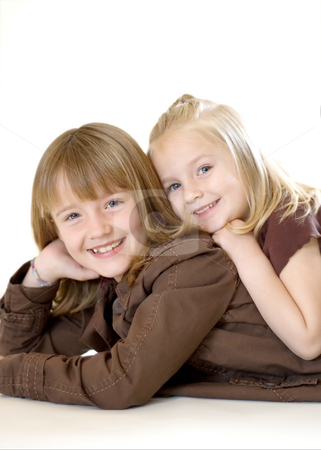 Two Sisters Posing - Vertical stock photo, Two cute young sisters posing together in a studio. Vertically framed shot isolated against a white studio background. The older sister has her face resting on her hand. Both are smiling at the camera by Orange Line Media