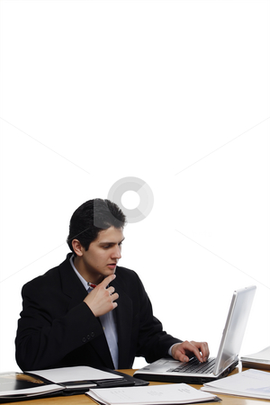 Deep in Thought Businessman stock photo, Businessman, at a desk, deep in thought with his finger on his chin.  Vertical isolated on white. by Orange Line Media