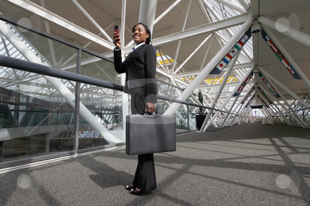 Woman Taking a Picture on Her Camera phone stock photo, Businesswoman standing in an office atrium smiling as she takes a picture on her cellphone. Lobby has international flags adorning it. Horizontally framed shot. by Orange Line Media