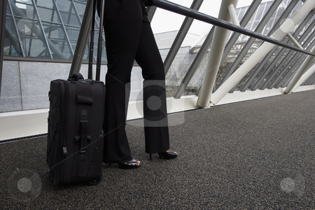Businesswoman With Luggage stock photo, Businesswoman with a rollaboard standing in a walkway. Horizontally framed shot focused on the woman's legs. by Orange Line Media