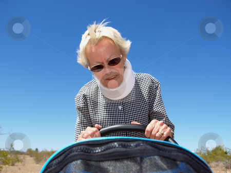 Grandmother Pushing Stroller in Desert stock photo, An isolated shot of a grandmother, wearing whiplash neck-brace, pushing a baby stroller. by Orange Line Media
