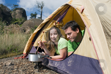 Couple Camping in Tent, Cooking stock photo, Young smiling couple lying in a tent cooking on cookstove. by Orange Line Media