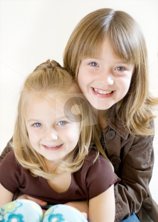 Two Sisters Posing - Vertical stock photo, Two cute young sisters posing together in a studio. Vertically framed shot isolated against a white studio background. The older sister is hugging the younger one. Both are smiling at the camera by Orange Line Media