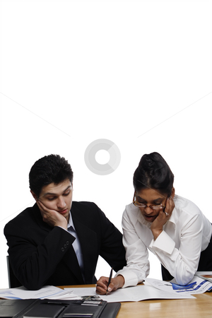 Teamwork - Concentration stock photo, Businessman and businesswoman looking intently at their paperwork, with their hand on their faces.  Vertical isolated on white. by Orange Line Media