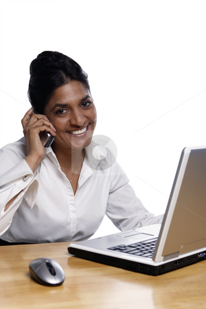 Smiling Businesswoman at Desk stock photo, Smiling businesswoman at a desk talking at cellphone and using a laptop, shot isolated and vertical.  Subject looking at camera. by Orange Line Media