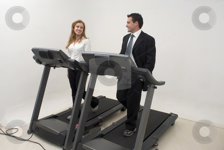 Businesspeople on Treadmill - Horizontal stock photo, Two businesspeople (male and female) running on a treadmill and looking at each other and smiling by Orange Line Media