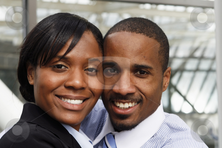 Business Couple - Close-up stock photo, A businessman, dressed business causal, with his arm around a businesswoman dressed in a suit.  The couple are standing very close to each other. by Orange Line Media