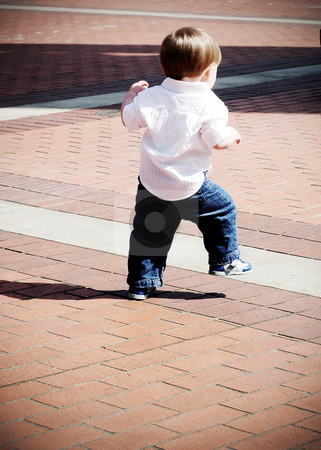 Young Boy Playing stock photo, Cute young boy running outside in the sunshine on a brick pavement by Orange Line Media