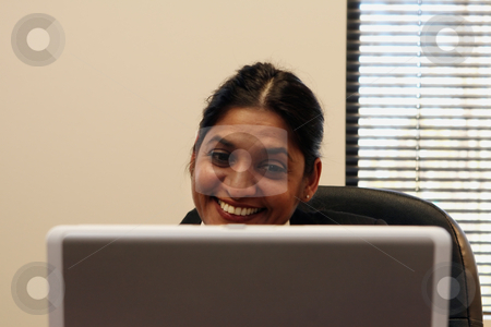 Smiling at Laptop stock photo, Businesswoman smiling at her laptop. by Orange Line Media