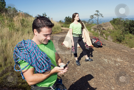 Man and Woman Camping stock photo, Attractive young man with climbing gear showing off his compass with an attractive woman in the background. Couple is enjoying a camping trip together. Horizontally framed shot. by Orange Line Media