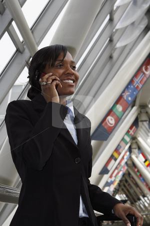 Businesswoman talking on her cellphone stock photo, Vertically framed shot of a smiling businesswoman stopping in a lobby while talking on her cellphone. She has her rollaboard luggage with her. by Orange Line Media