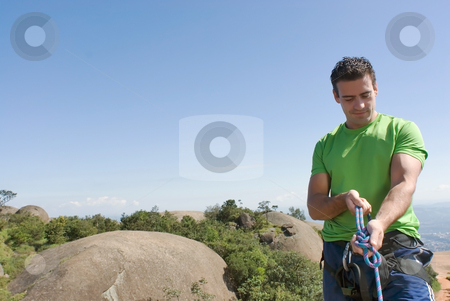 Man Checking Climbing Harness - Horizontal stock photo, Zoomed out shot of an athletic young climber checking his ropes and harness. Horizontal shot set against a clear blue sky. Subject on the right side of the composition by Orange Line Media