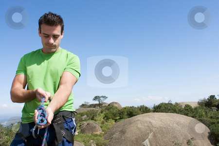 Man Checking Climbing Harness - Horizontal stock photo, Zoomed out shot of an athletic young climber checking his ropes and harness. Horizontal shot set against a clear blue sky. Subject on the left side of the composition by Orange Line Media