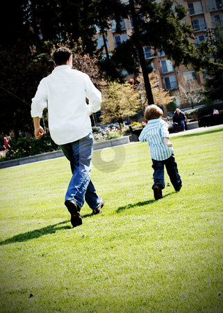 Father and Son stock photo, Father and son running together in a grassy field during the summer. High-key processing by Orange Line Media