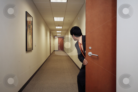 Businessman Sneaking Around - Horizontal stock photo, Horizontally framed shot of a young businessman peering into an empty hallway through a doorway. He is facing away from the camera by Orange Line Media
