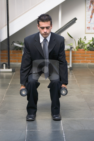 Businessman doing Squats stock photo, Businessman, in a suit, doing squats with dumbbells in a gym. by Orange Line Media