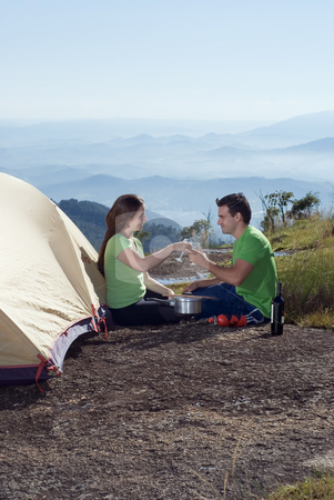 Couple Camping, Making a Toast - Vertical stock photo, Young smiling couple, sitting next to a tent, clinking wine glasses together making a toast.  In the background are beatiful clouds and mountains. by Orange Line Media