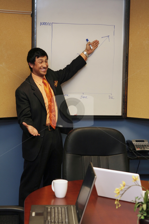 Businessman Giving a Presentation stock photo, Young businessman smiling as he presents at a whiteboard by Orange Line Media