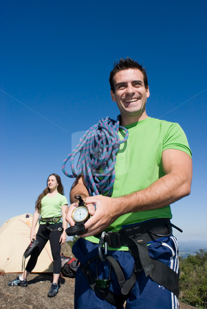 Camping Couple stock photo, Attractive young man with climbing gear showing off his compass with an attractive woman in the background. Couple is enjoying a camping trip together. by Orange Line Media