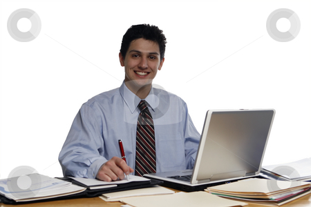 Young Smiling Businessman stock photo, Young, businessman sitting at desk smiling at the camera.  Shot horizontal isolated on white. by Orange Line Media