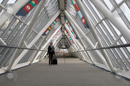 Businesswoman in Walkway stock photo, Businesswoman walking through a walkway / skybridge pulling her luggage behind her. The walkway is lined with flags. Horizontally framed shot with the woman walking towards the camera. by Orange Line Media