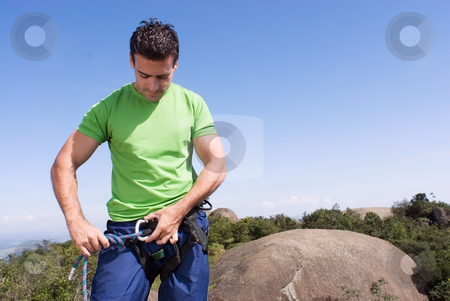 Man Checking Climbing Harness - Horizontal stock photo, Athletic young climber checking his gear and climbing harness. Horizontal shot set against a blue sky. by Orange Line Media