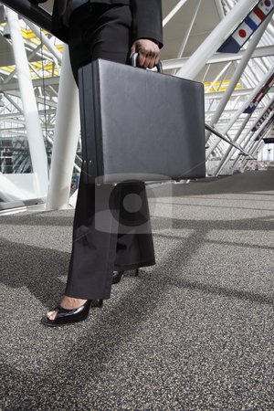 Woman with Briefcase stock photo, Close up of a businesswoman's legs and briefcase as she strides through an office lobby. Vertically framed shot. by Orange Line Media