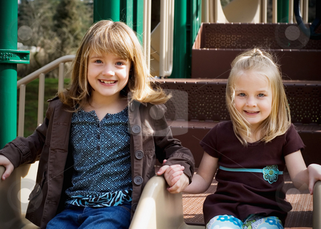 Seated Sisters stock photo, Two cute young sisters holding hands and sitting next to each other in an outdoor playground by Orange Line Media