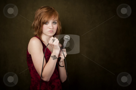Young girl on a green background with microphone stock photo, Pretty young girl with red hair on a green background with microphone by Scott Griessel