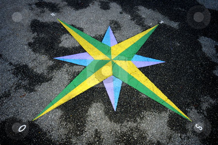 Compass rose stock photo, A colourful compass rose set into asphalt, which is slightly wet. Photoraph taken in a French-speaking country, which is why west is signified by an 'O' (ouest). by Alistair Scott