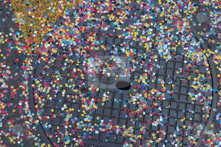 Confetti on a drain stock photo, Confetti scattered across the metal cover of a drain in the street, the random scattering of the confetti contrasting with the regular grid on the manhole cover. by Alistair Scott
