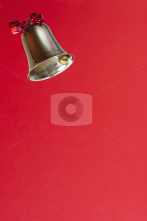 Ringing bell on red background stock photo, A ringing bell, decorated with a red ribbon. on bright re background, Space for text. by Alistair Scott