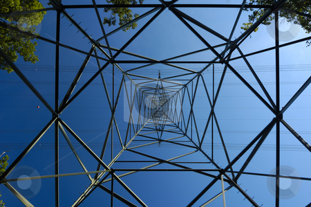 Metal web. stock photo, Inside an electricity pylon, surrounded by a few green trees, looking directly up at the clear blue sky. It is as if the pylon forms a metal spider's web. by Alistair Scott