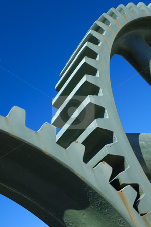 Gears stock photo, Two old interlocking gear wheels,  slightly rust-streaked, from some unidentifiable piece of machinery, set against a clear blue sky. Space for text. by Alistair Scott