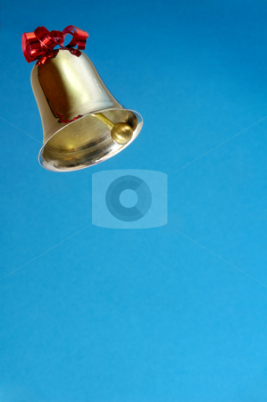 Ringing bell on blue background stock photo, A ringing bell, decorated with a red ribbon. on plain blue background, Space for text. by Alistair Scott
