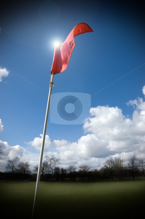 Golf Flag fluttering in the wind stock photo, Red golf flag fluttering in the wind lit by the sun by Peter Cox