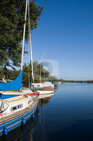 Moored sailing yachts stock photo, Moored sailing yachts moored on a calm lake by Peter Cox