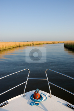 Boat on a River stock photo, Bow of a white boat cruising along a calm blue river past golden yellow reedbeds looking towards the distant horizon by Peter Cox