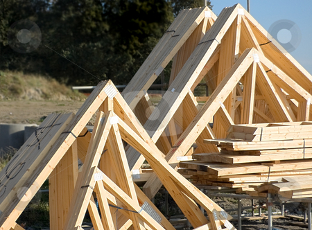Wooden Roof Trusses stock photo, Wooden roof trusses stacked together on a building site by Peter Cox