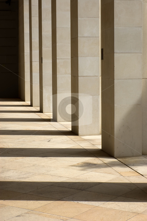 Stone Columns stock photo, Stone columns lit from the side with long shadows cast upon the ground by Peter Cox