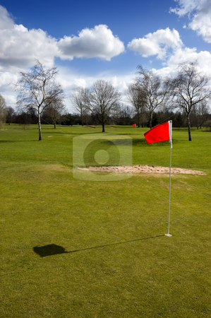 Golf Course stock photo, Red flag on the putting green of a golf course on a sunny winter day by Peter Cox