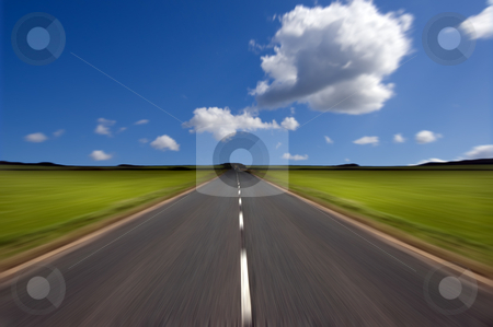 Road with motion blur stock photo, Rural road stretching out into the distance with motion blur under a big expanse blue sky.  Concepts could include - road to success, new beginnings, follow your dreams etc by Peter Cox