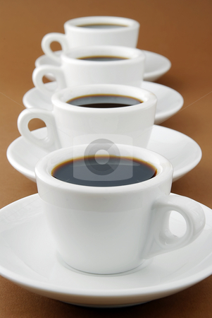 Espresso row stock photo, A row of full espresso cups on saucers by Paul Turner