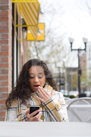 Surprising Text Message stock photo, An attractive Indian woman texting or searching the web on her cell phone while seated at a table outdoors. by Todd Arena