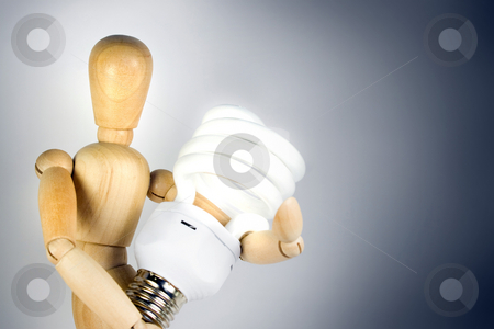 Compact Fluorescent Bulb stock photo, A wooden model grasping a compact fluorescent light bulb.  Great for energy savings or going green concepts. by Todd Arena