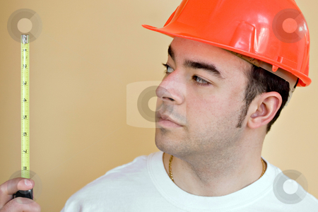 Worker Measuring stock photo, A young construction worker using a tape measure. Plenty of copyspace. by Todd Arena
