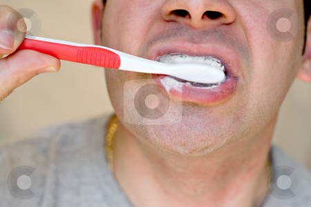 Brushing His Teeth stock photo, A closeup of a young man while he is brushing his teeth. by Todd Arena