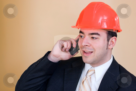 Industrial Professional stock photo, A man in a business suit and hard hat talks on his cell phone.  He could be a custom home builder or even an engineer or architect. by Todd Arena
