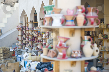 Traditional Arabian market stock photo, Traditional Arabian market in Oman with various ceramic items on display, including incense burners and water pots. by Nicolaas Traut