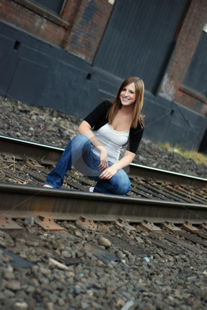 Teen Kneeling in Between Train Tracks stock photo, Outdoor shot of a cute smiling teenage girl keeling in between train tracks. by Orange Line Media